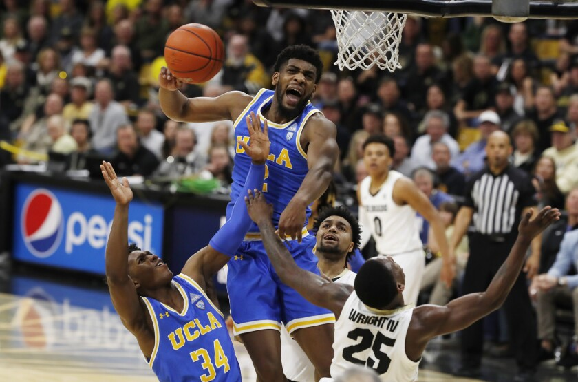 UCLA forward Cody Riley, center, blocks a shot by Colorado guard McKinley Wright IV, right, as UCLA guard David Singleton pulls in the loose ball in the second half on Feb. 22 in Boulder, Colo.