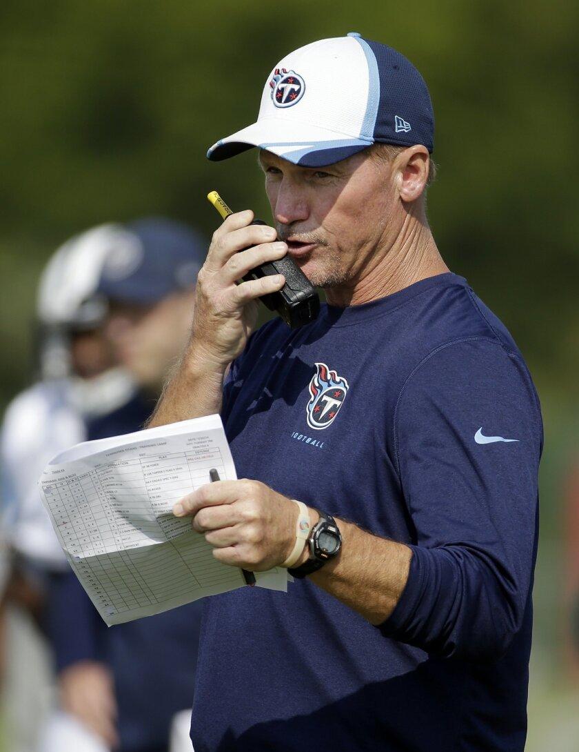 Tennessee Titans head coach Ken Whisenhunt talks on a walkie-talkie during NFL football training camp Tuesday, July 29, 2014, in Nashville, Tenn. (AP Photo/Mark Humphrey)