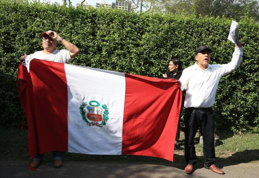 Critics of Peruvian former President Alan Garcia hold up the national flag outside the Uruguayan Embassy in Lima on Sunday, Nov. 18. EFE-EPA/Ernesto Arias
