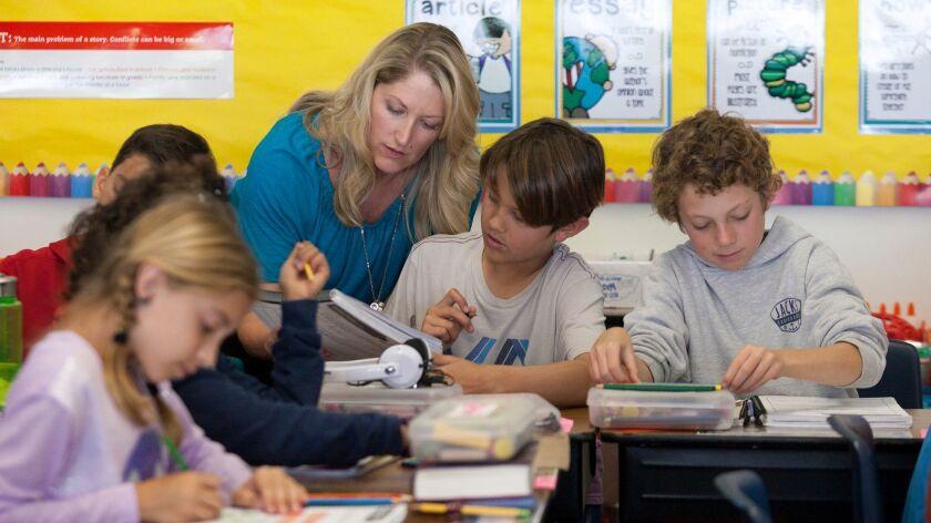 NEWPORT BEACH, CA, February 25, 2015 -- Fifth grade teacher Season Leech helps Riley Chester with a