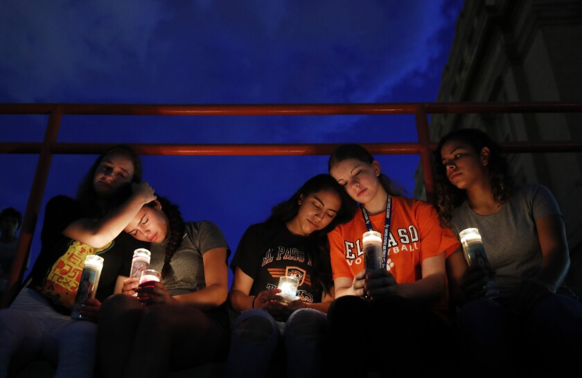 Mourners of the U.S. mass shooting in El Paso embrace each other at a vigil, seated with glowing candles.