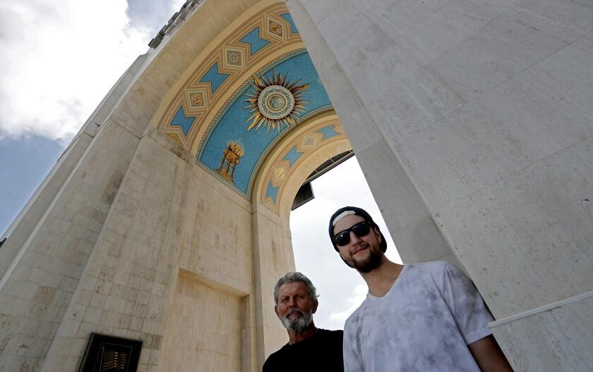 Mick Rosien, izquierda, y su hijo Nick posan debajo del mural en el arco principal del Coliseo. El papá de Mick, Heinz Rosien, pintó el mural, junto a su hermano, Igor, en 1969.