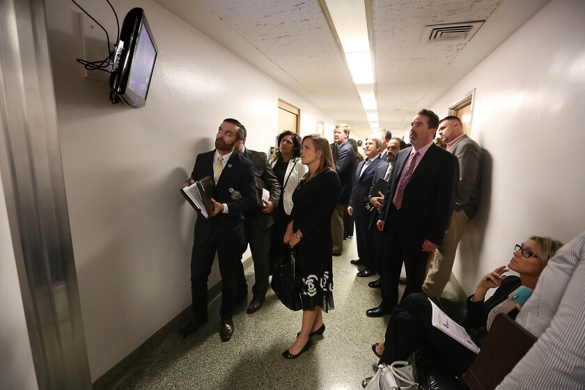 Lobbyists and advocates watch the action in the state Assembly on a television outside the chambers on Aug. 27, 2014.