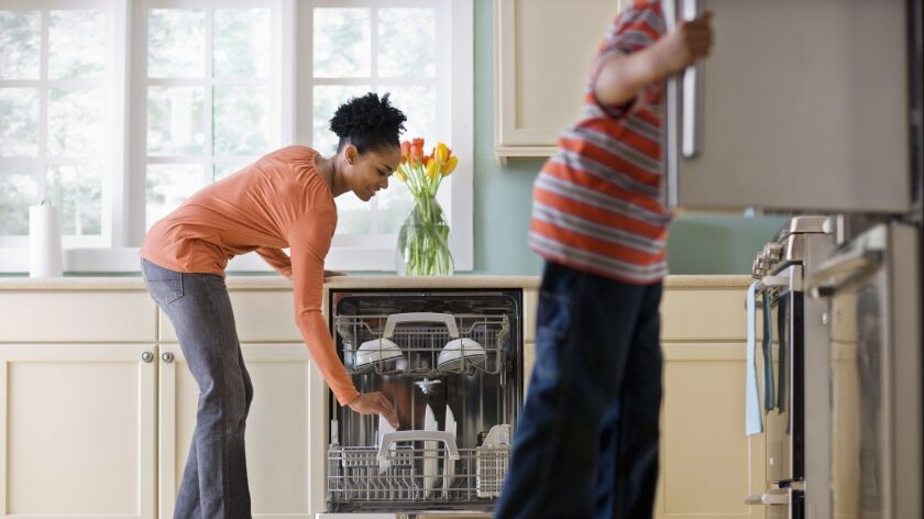 Woman Unloading Dishwasher While Son Looks in Refrigerator. (Fuse/Getty Images) The costs associated