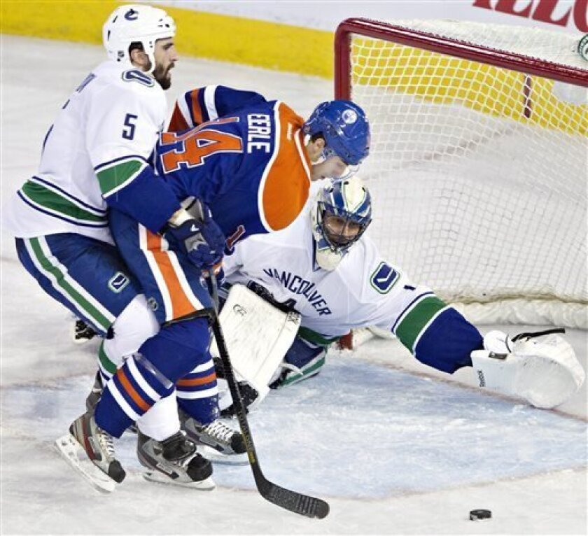 Vancouver Canucks goalie Roberto Luongo makes the save on Edmonton Oilers' Jordan Eberle as Jason Garrison, left, defends during the second period of an NHL hockey game in Edmonton, Alberta, on Saturday, March 30, 2013. (AP Photo/The Canadian Press, Jason Franson)