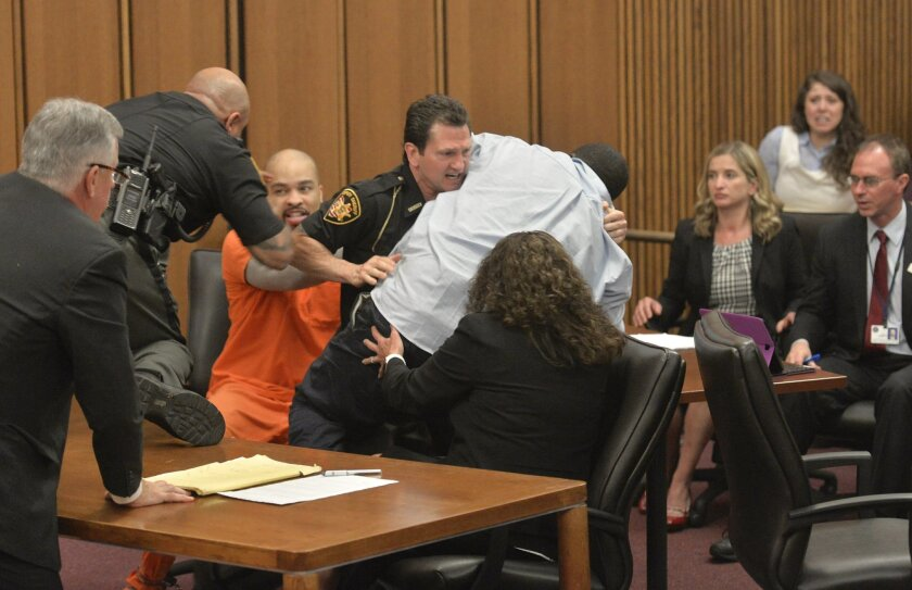 A court officer tackles the father of one of three victims of Ohio serial killer Michael Madison, left, who leaped over a table to attack the defendant in court just minutes after the judge pronounced a death sentence in Cuyahoga County Common Pleas Court Thursday, June 2, 2016, in Cleveland. Van T
