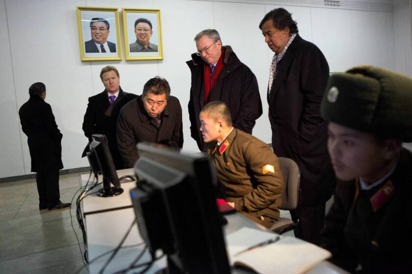 Google Executive Chairman Eric Schmidt, red scarf, and former New Mexico Gov. Bill Richardson, standing, right, watch North Korean soldiers working on computers at the Grand Peoples Study House in Pyongyang. The two are on what they described as a private humanitarian visit.