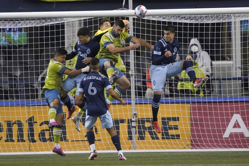 Vancouver Whitecaps goalkeeper Thomas Hasal, center rear, punches away a shot during the first half of the team's MLS soccer match against the Seattle Sounders, Saturday, Oct. 9, 2021, in Seattle. (AP Photo/Ted S. Warren)