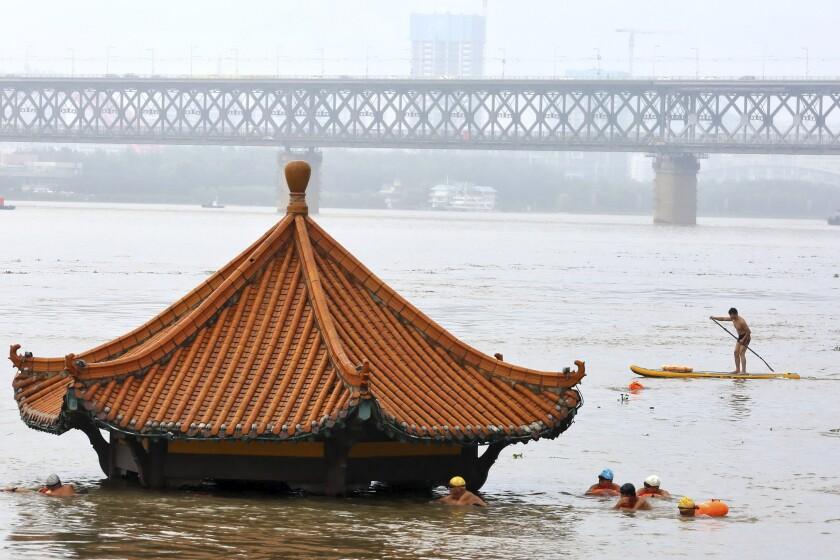 Residentes nadan junto al un pabellón sumergido por la crecida del río Yangtsé en Wuhan, en el centro de China, el miércoles, 8 de julio del 2020. Socorristas buscaban el miércoles a nueve personas desaparecidas en un alud, en medio de inundaciones en gran parte del país. (Chinatopix Via AP)