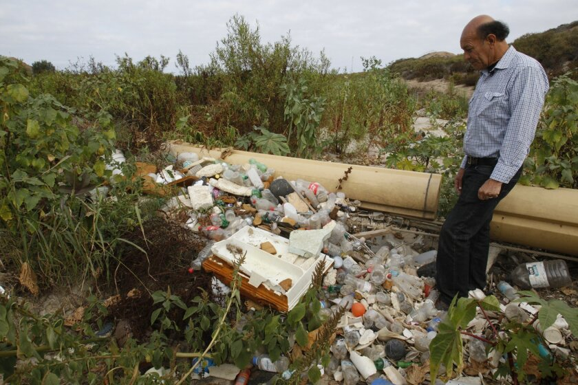 Oscar Romo shows soem of the trash captured during the last year at a settling basin in the U.S. where the waters from Los Laureles Canyon in Tijuana wash in the Tijuana River Valley. The floating boom captured these plastics and is due to be cleaned out before the arrival of this years wet season.