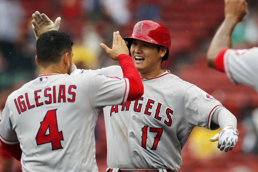 Angels designated hitter Shohei Ohtani, right, celebrates with Jose Iglesias after hitting his two-run home run.