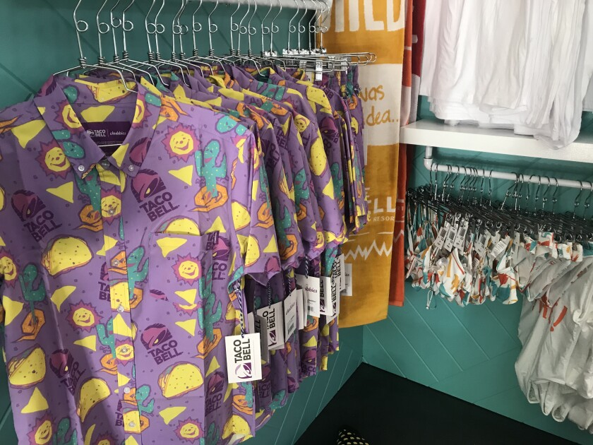 Taco Bell-themed shirts and other merchandise is for sale in the gift shop.