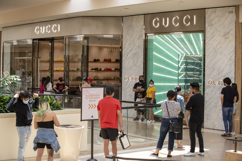 Shoppers wait in line outside Gucci last week as South Coast Plaza in Costa Mesa reopens.