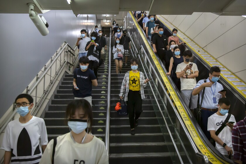 Commuters wearing face masks to protect against the spread of the new coronavirus walk through a subway station in Beijing, Thursday, July 9, 2020. (AP Photo/Mark Schiefelbein)