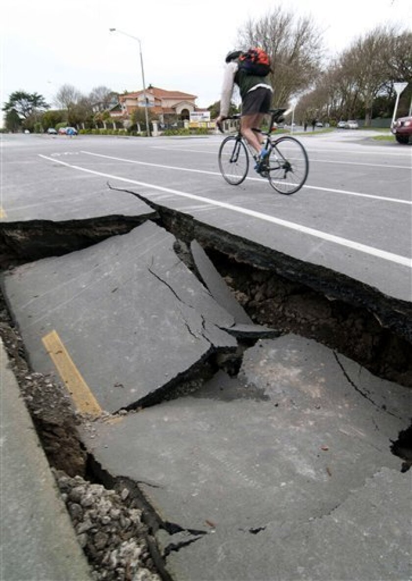 A person cycles past a damaged road near the Avon River following Saturday's powerful 7.1-magnitude earthquake, in Christchurch, New Zealand, Sunday, Sept. 5, 2010. The quake that smashed buildings, cracked roads and twisted rail lines around the New Zealand city also ripped a new 11-foot- (3.5 meter-) wide fault in the earth's surface, officials said Sunday. (AP Photo/NZPA, David Alexander)