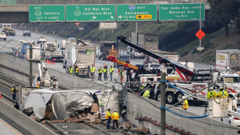 Crews work around the wreckage after a FedEx truck on the 210 Freeway in Pasadena toppled onto the tracks of the Metro Gold Line after being rear-ended by a driver in a sedan in April 2018.
