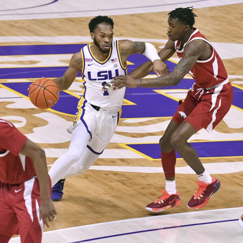 LSU guard Javonte Smart (1) drives past Arkansas guard Davonte Davis (4) during the first half of an NCAA college basketball game Wednesday, Jan. 13, 2021, in Baton Rouge, La. (Hilary Scheinuk/The Advocate via AP)