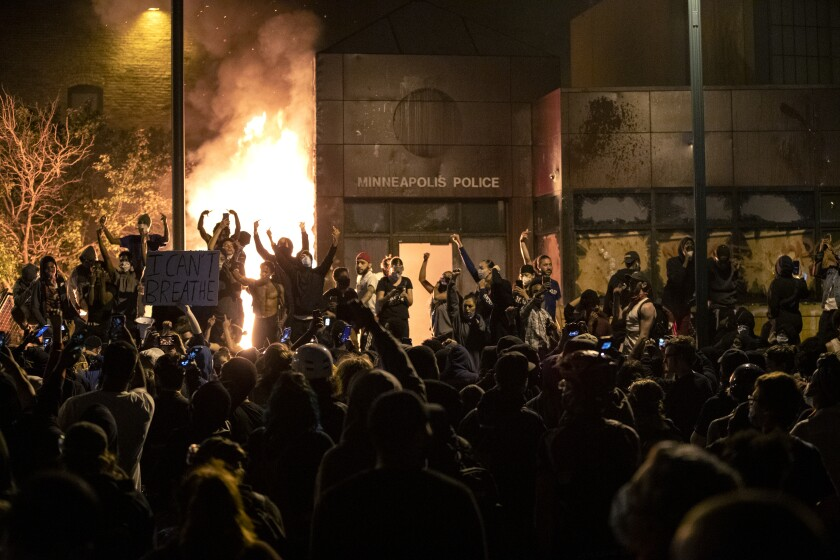 EDS NOTE: OBSCENITY - Protesters gesture after the Minneapolis police 3rd Precinct building was set on fire Thursday night, May 28, 2020, during demonstrations over the Monday death of George Floyd in Minneapolis police custody. (Carlos Gonzalez/Star Tribune via AP)