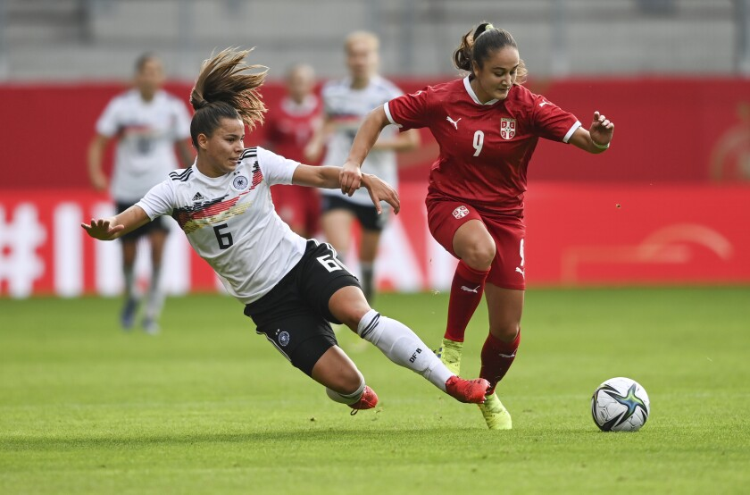 Germany's Lena Sophie Oberdorf, left, challenges for the ball with Serbia's Nina Matejic during the women soccer World Cup qualification match between Germany and Serbia in Chemnitz, Germany, Tuesday, Sept. 21, 2021. (Hendrik Schmidt/dpa via AP)