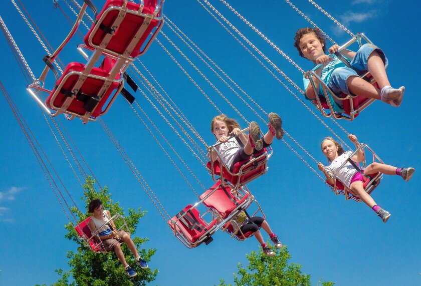 """This July 1, 2014 photo provided by Little Prince Park shows children on swings at the park's opening day in Ungersheim, in the Alsace region of eastern France. The park is themed on one of French literature's most beloved characters, """"The Little Prince,"""" or """"Le Petit Prince,"""" from the 1943 novella by Antoine de Saint-Exupery. The park offers gentle attractions for young children. (AP Photo/Little Prince Park, Michel Caumes)"""