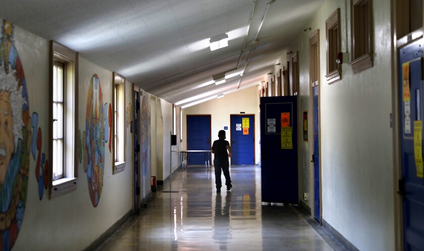 The silhouette of a child walking down a school hallway.