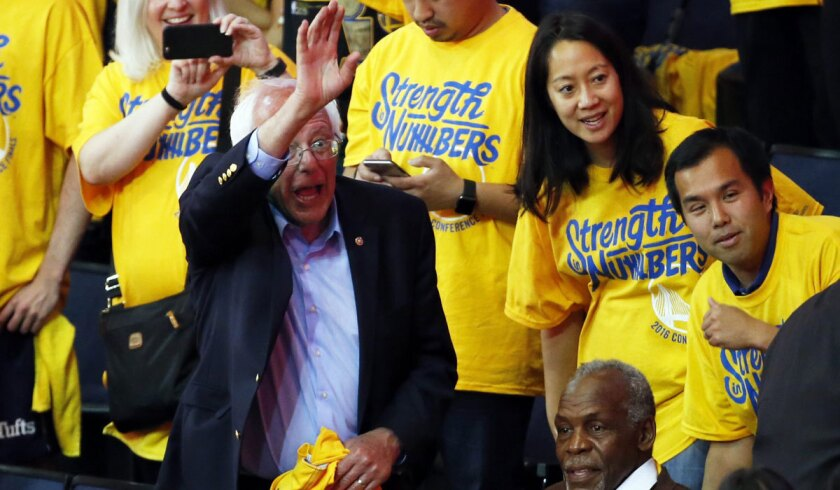Democratic presidential candidate Bernie Sanders attends Game 7 of the Western Conference finals Monday in Oakland, alongside actor Danny Glover, bottom right.