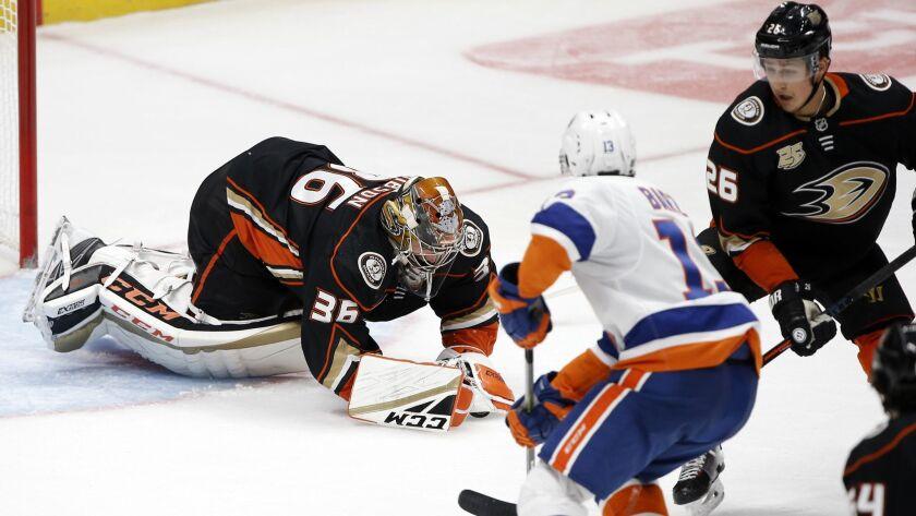 Anaheim Ducks goaltender John Gibson, left, covers up a loose puck as Anaheim Ducks defenseman Brand