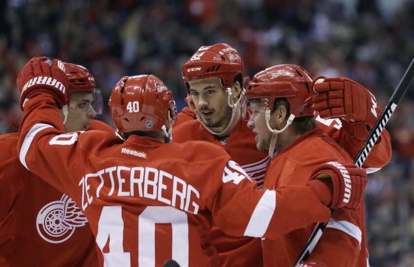 Detroit Red Wings left wing Henrik Zetterberg (40), of Sweden, congratulates defenseman Jonathan Ericsson, center, of Sweden, after Ericsson scored a goal during the second period of an NHL hockey game against the Colorado Avalanche, Friday, Feb. 12, 2016, in Detroit. (AP Photo/Carlos Osorio)