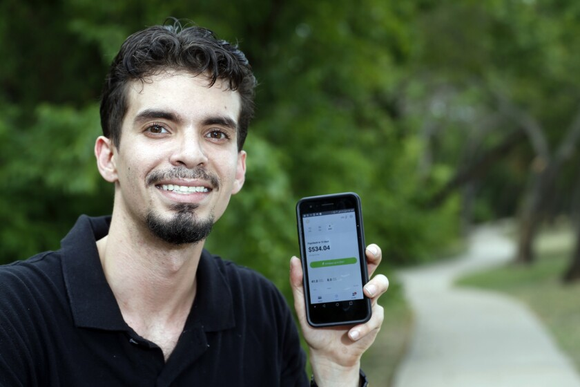 Luis Vazquez. 27, an overnight support manager at Walmart in Dallas, pictured on Saturday, July 28, 2018, uses the Instapay app, developed by technology company Even, to assist him with his finances. The phone app allows users to access up to 50 percent of their earned wages during a pay period and avoid payday loans.