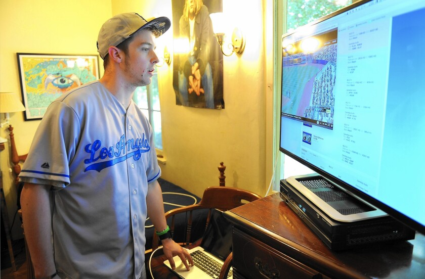 John Franks connects his laptop computer to his television to get the Dodgers cable experience.