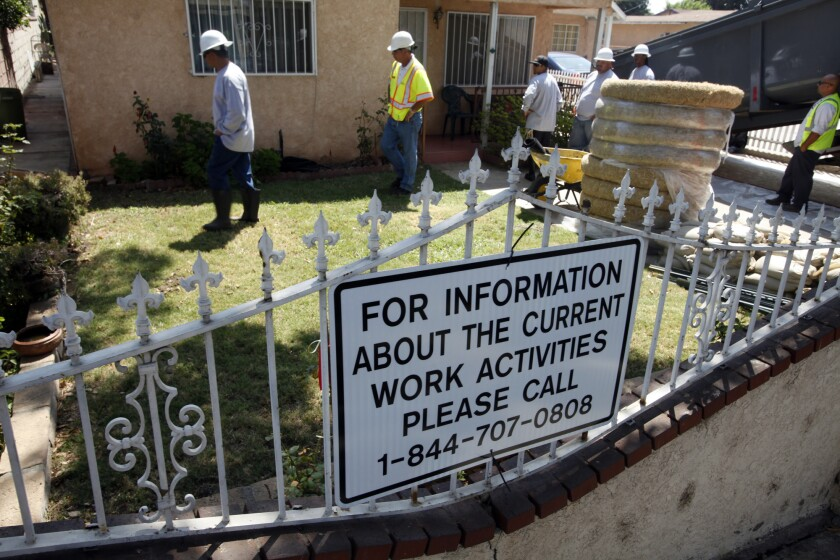 Crews hired by Exide Technologies began work Monday to remove lead-contaminated soil from two homes in Boyle Heights under orders from California toxic waste regulators.