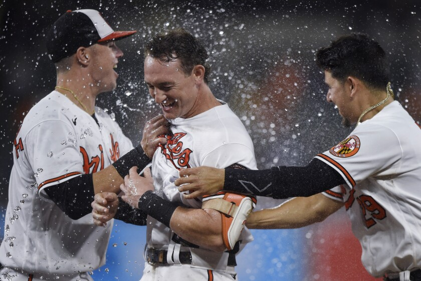 Baltimore Orioles' Austin Hays, center, is congratulated by Ryan Mountcaste, left, and Ramon Urias after driving in the winning run against the New York Yankees during the 10th inning of a baseball game Thursday, Sept. 16, 2021, in Baltimore. The Orioles won 3-2. (AP Photo/Gail Burton)