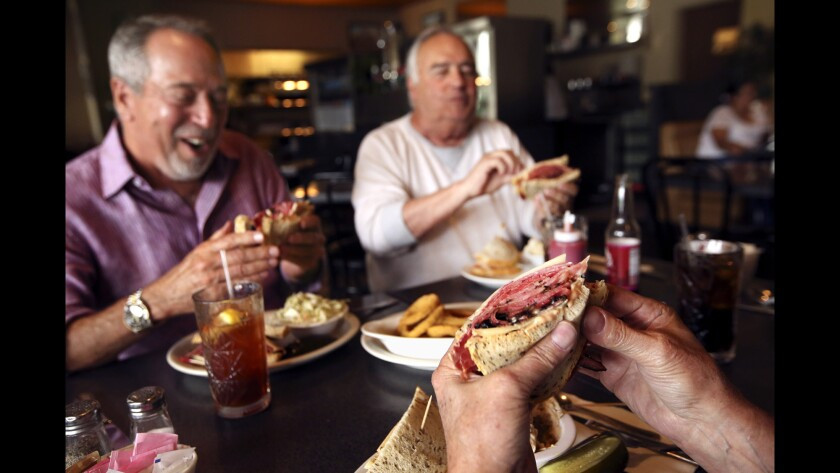 Customers Harvey Rosen, left, Larry Berkowitz, right, and Peter Kares, foreground, enjoy the No. 35 sandwich -- pastrami, corned beef and Swiss cheese on rye, with Russian dressing -- at Victor's Square Restaurant in Hollywood. After 32 years, owner Bill Gotti recently closed the popular deli.