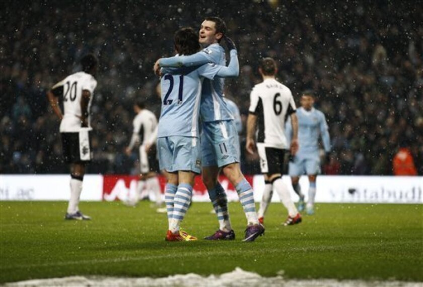 Manchester City's Adam Johnson, center, celebrates with teammate David Silva after forcing an own goal against Fulham during their English Premier League soccer match at The Etihad Stadium, Manchester, England, Saturday, Feb. 4, 2012. (AP Photo/Jon Super)