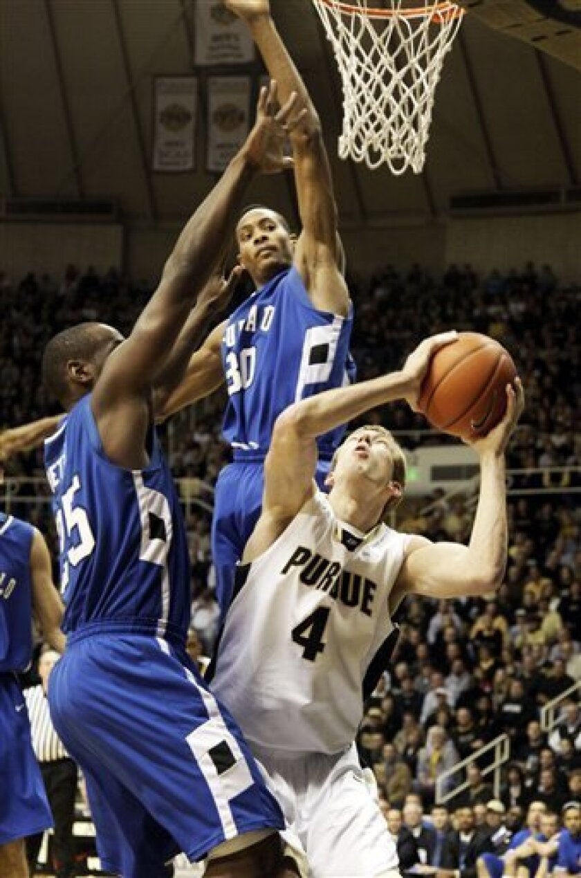 Purdue forward Robbie Hummel, right, looks to shoot under the defense of Buffalo forward Titus Robinson , center, and guard Calvin Betts during the first half of a NCAA college basketball game in West Lafayette, Ind., Saturday, Dec. 5, 2009. (AP Photo/AJ Mast)