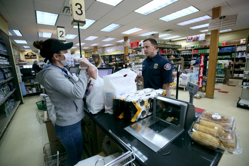 Spencer Hammond, a firefighter-paramedic with the Glendale Fire Department, purchases groceries at Pacifc Food Mart from cashier Arga Esaghlian. Employees at the store are now wearing face masks and gloves as a safety precaution because of the coronavirus outbreak.
