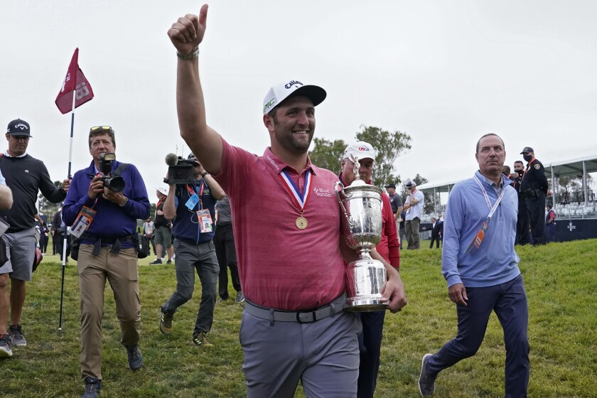 Jon Rahm, of Spain, leaves the 18th green with the champions trophy after the final round of the U.S. Open Golf Championship, Sunday, June 20, 2021, at Torrey Pines Golf Course in San Diego. (AP Photo/Marcio Jose Sanchez)