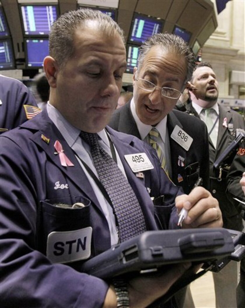 FILE - In this March 17, 2011 file photo, traders Joel Lucchese, left, and Vito Perri, center, work on the floor of the New York Stock Exchange. (AP Photo, file)