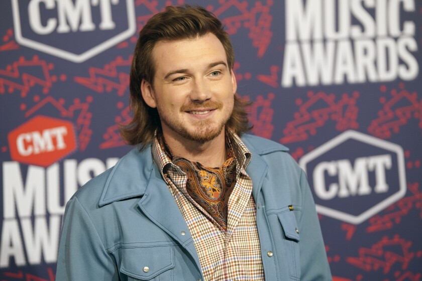 Morgan Wallen smiles while wearing a light blue coat with a mullet hairstyle