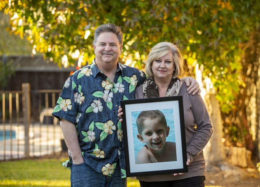 Richard and Andrea Dunn hold a photograph of their late son Julian, who died in 2013.