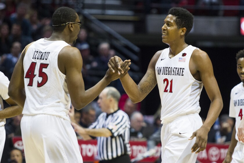 Aztecs junior Malik Pope, right, celebrates with Valentine Izundu during the team's 74-55 win Saturday at Viejas Arena. Pope made a strong return after missing six games.