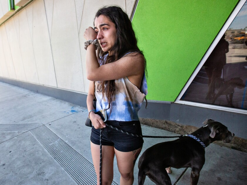 Christine Gamez of Fullerton returns her fostered bulldog, Tyson, to a shelter in South Los Angeles.