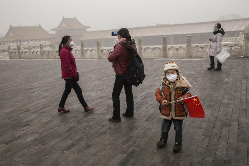 A Chinese boy wears a mask as protection from the pollution as he stands with a China flag in Beijing's Forbidden City during a high-pollution day on Tuesday.