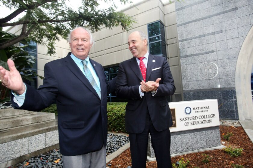 Philanthropist Denny Sanford, left, stands with National University Chancellor Michael Cunningham as he thanks the crowd after the unveiling of a monument for the Sanford College of Education. The school's Sanford Inspire Program uses some of the education principles developed by Teach for America.