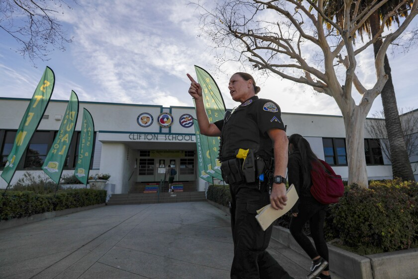 Police officer monitors traffic as students arrive Thursday at Clifton Middle School in Monrovia