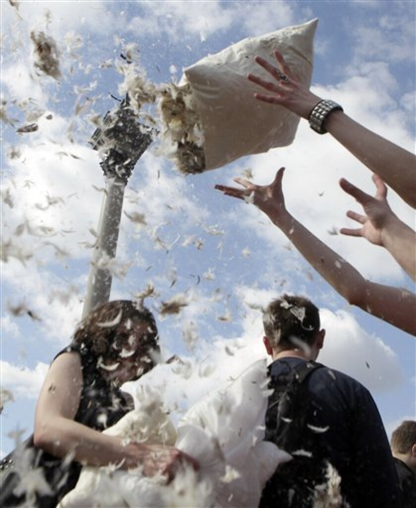 Young people take part in a pillow fight on Pillow Fight Day at the Zamkowy square in Warsaw, Poland, Saturday, April 2, 2011. (AP Photo/Czarek Sokolowski)
