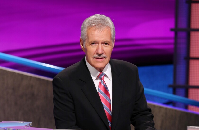Alex Trebek leaning over the 'Jeopardy!' podium