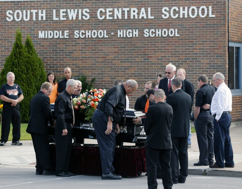 The casket of race car driver Kevin Ward Jr., is taken from a hearse before being carried into South Lewis Central School before a funeral on Thursday, Aug. 14, 2014, in Turin, N.Y. Ward died after being struck by NASCAR driver Tony Stewart's car during a race last weekend at a dirt track in western New York. (AP Photo/Mike Groll)