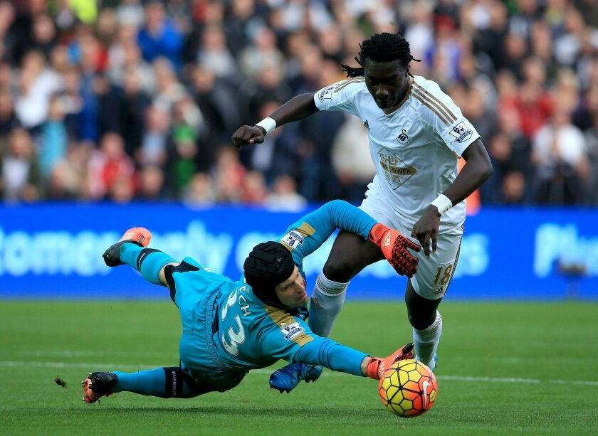 Arsenal goalkeeper Petr Cech dives in front of Swansea City's Bafetimbi Gomis during their English Premier League soccer match at the Liberty Stadium, Swansea, England, Saturday Oct. 31, 2015. (Nick Potts / PA via AP) UNITED KINGDOM OUT - NO SALES - NO ARCHIVES