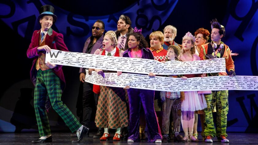 """Willy Wonka (played by Noah Weisberg, left) rolls out a bit of paperwork as he leads prizewinners into his plant in the national tour of """"Charlie and the Chocolate Factory."""""""